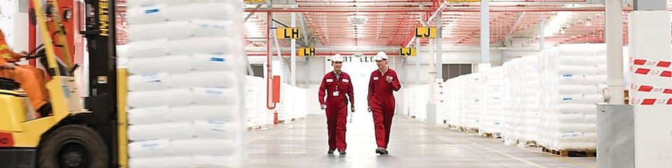 Two employees walking in a factory